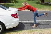 Young woman pushing her broken down car — Stock Photo