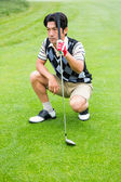 Crouching golfer holding club looking away  — Stok fotoğraf