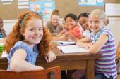 Cute pupils writing at desk in classroom — Stockfoto