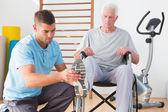 Coach helping invalid senior — Stock Photo