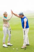 Couple high fiving on the golf course — Stock Photo