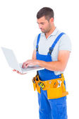 Carpenter in blue overalls using laptop — Stockfoto