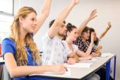 Students raising hands in classroom — Stock Photo