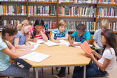 Cute pupils writing at desk in library  — Stock Photo