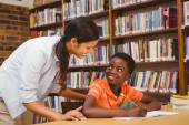 Teacher assisting boy with homework in library — Stock Photo