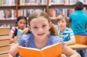Cute pupils reading in library — Stock Photo