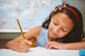 Little girl writing book in classroom — Stock Photo
