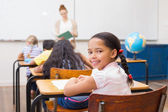 Cute pupil smiling at camera in classroom — Stock Photo