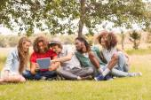 Happy friends in the park looking at tablet — Stock Photo