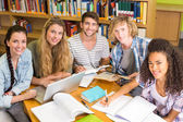 College students doing homework in library — Stockfoto