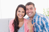 Happy young woman showing ring while sitting with man  — Stock Photo