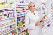 Serious pharmacist holding clipboard — Stockfoto