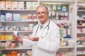 Smiling senior doctor showing medication — Foto de Stock