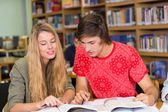 College students doing homework in library — Stok fotoğraf