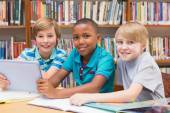 Cute pupils using tablet computer in library — Stock Photo