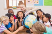 Cute pupils and teacher in classroom with globe  — Stock Photo