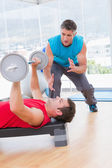 Trainer assisting man with dumbbells — Stock Photo