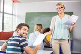 Teacher handing paper to student in class — Stock Photo