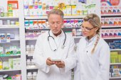 Pharmacist speaking with his trainee about medicine — Stock Photo