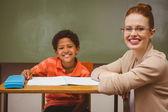 Оказание помощи маленького мальчика с заданием в классе учитель — Стоковое фото