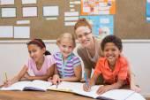 Učitel a žáci společně u stolu — Stock fotografie