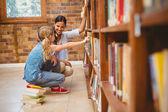 Teacher and little girl selecting book in library — ストック写真