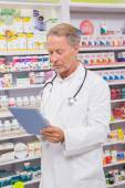 Concentrated senior pharmacist using tablet — Stock Photo