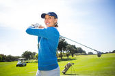 Lady golfer teeing off and smiling — Stock Photo