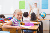 Cute pupil smiling at camera at his desk in classroom — Stock Photo