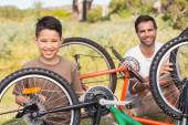 Father and son repairing bike together — Stok fotoğraf