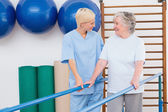Therapist helping senior woman to walk with parallel bars — Stock Photo
