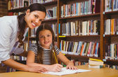 Teacher assisting little girl with homework in library — Stock Photo