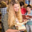 Female college student holding books in library — Stock Photo #68990767