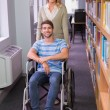 Smiling disabled student with classmate in library — Stock Photo #68990957