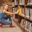 Cute little girl selecting book in library — Stock Photo #68991127