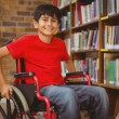 Portrait of boy sitting in wheelchair at library — Stock Photo #68991735