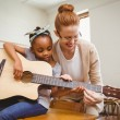 Teacher teaching girl to play guitar in classroom — Stock Photo #68992215