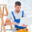 Repairman using laptop by ladder in office — Stock Photo #68992567