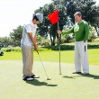 Golfer holding hole flag for friend putting ball — Stock Photo #68993067