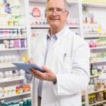 Smiling pharmacist using tablet pc — Stock Photo #68993339