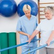 Senior woman walking with parallel bars with therapist — Stock Photo #68994113