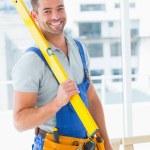 Repairman in overalls holding spirit level — Stock Photo #68994305