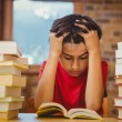 Tensed boy sitting with stack of books — Stock Photo #68995027