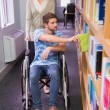 Smiling disabled student with classmate in library — Stock Photo #68995129