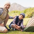 Father and son pitching their tent — Stock Photo #68995275