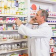 Focused pharmacist on the phone pointing medicine — Stock Photo #68995313