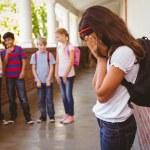 Sad schoolgirl with friends in background at school corridor — Stock Photo #68995669