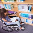 Smiling disabled student in library reading book — Stock Photo #68995999
