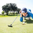 Female golfer blowing her ball on putting green — Stock Photo #68996113