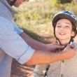 Father clipping on sons helmet — Stock Photo #68996663